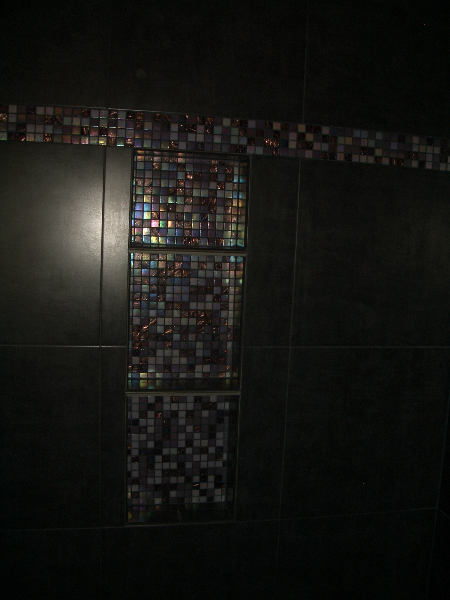 Glass shower niche in porcelain shower tile installation