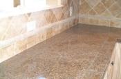 Granite tile countertops with travertine backsplash