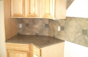 Porcelain backsplash with granite inserts and countertops