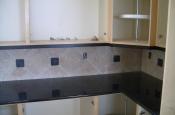 Porcelain kitchen backsplash with slate inserts and granite countertops