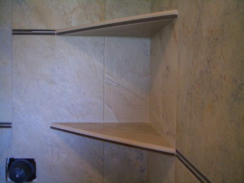 Close-up of shower shelves with glass pencil rail