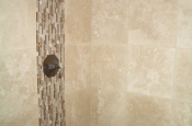 Travertine and glass master bathroom shower tile with oil-rubbed bronze installation in Fort Collins, Colorado