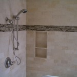 Travertine subway bathroom with glass inserts and niche