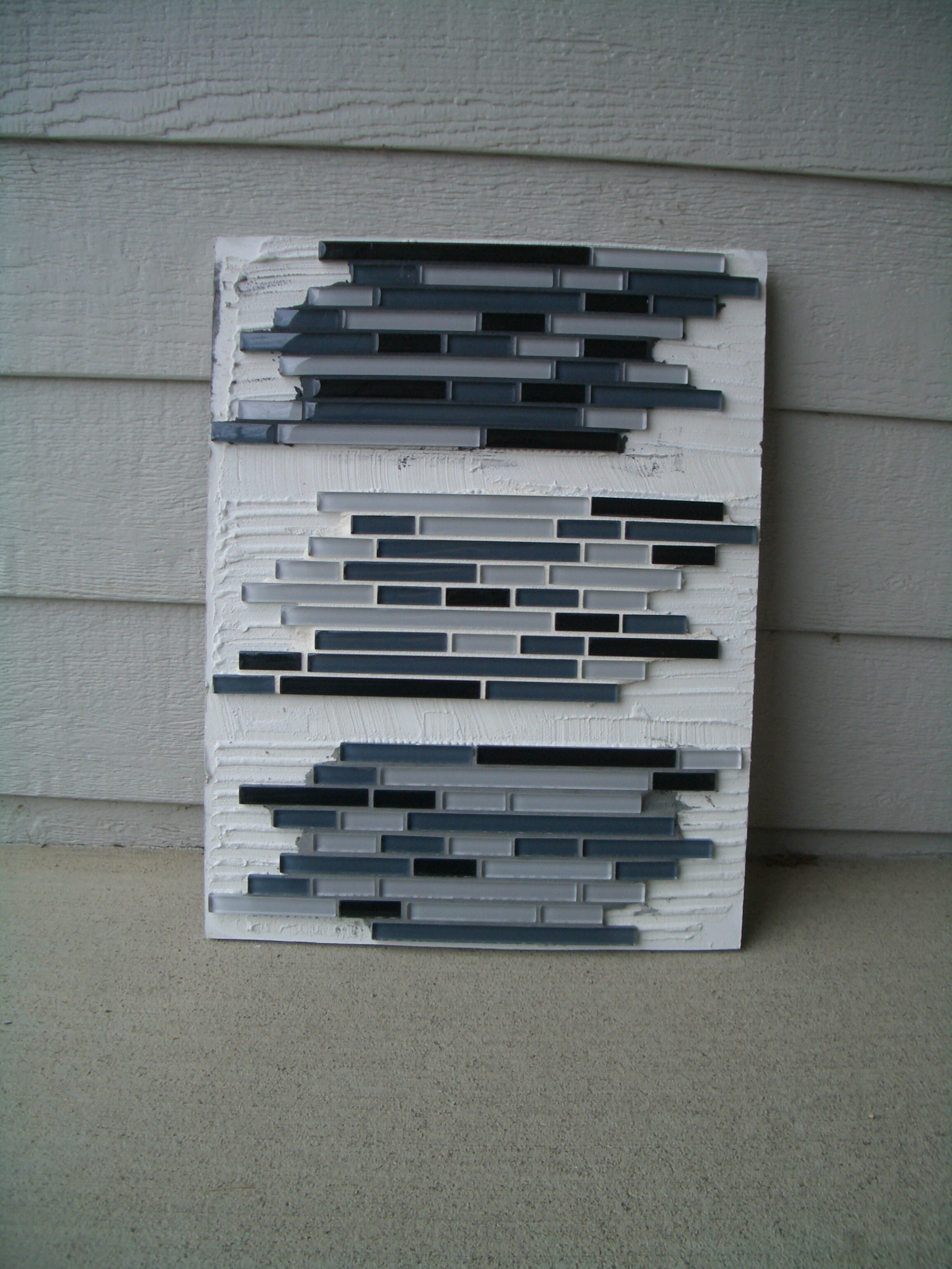 sample board showing different grout colors for glass tile